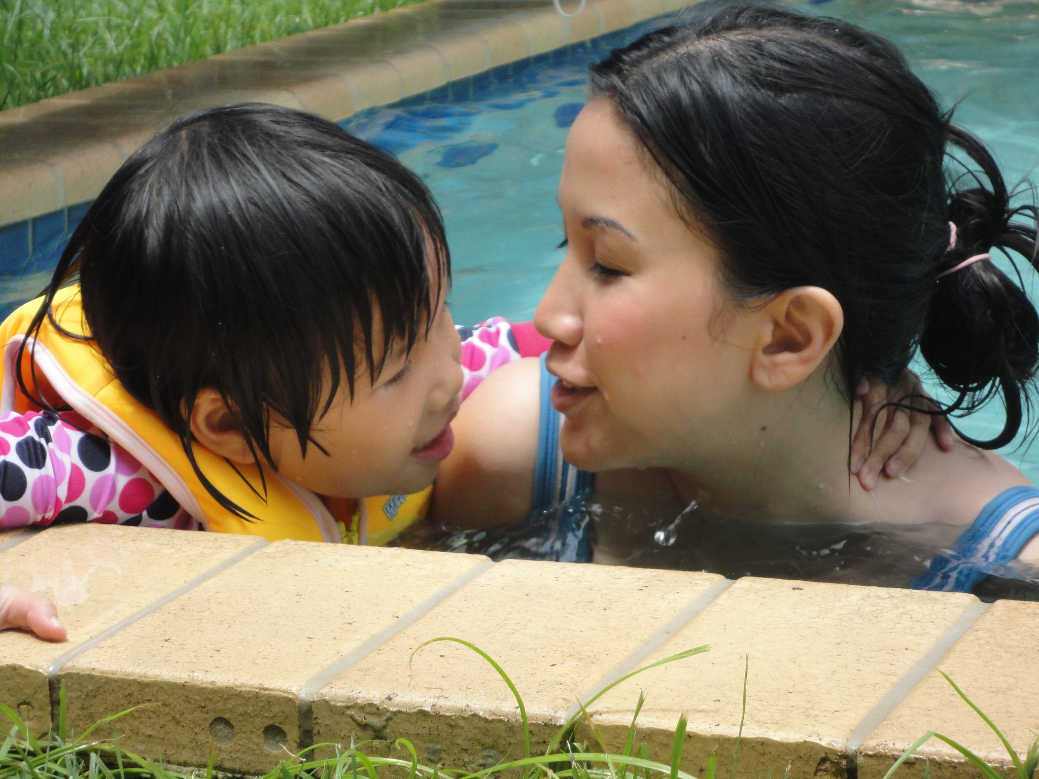 Mother and baby sharing a moment in a pool.