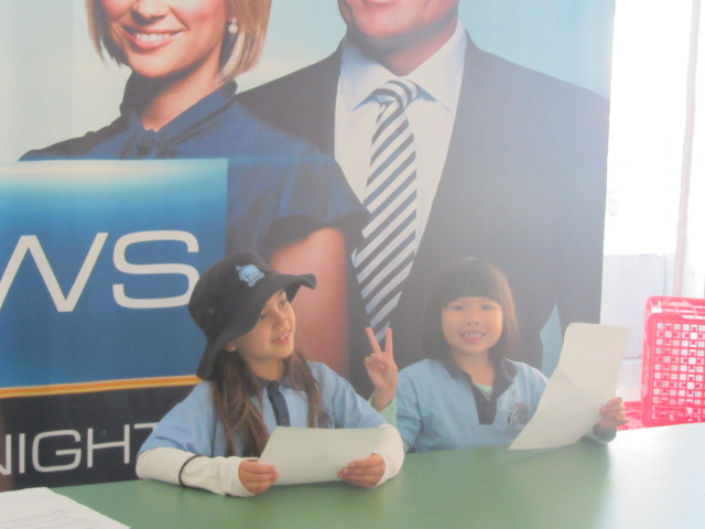Amanda and Lily reading the news at Out of the Box.