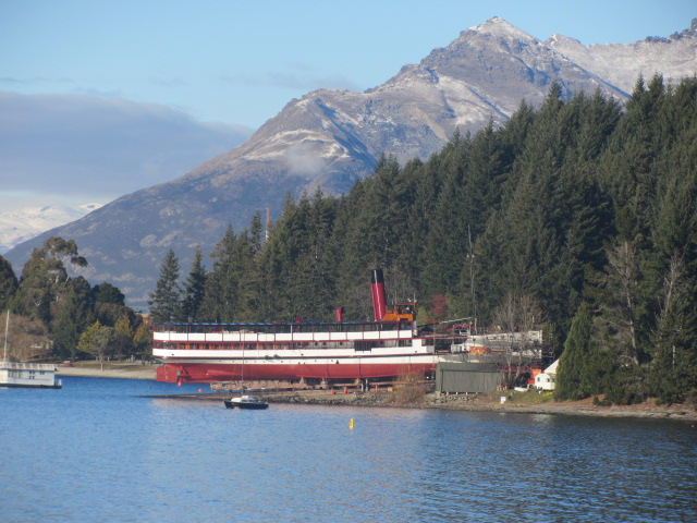 A picture of TS Earnslaw banked on the other side of Lake Wakatipu in Queenstown, New Zealand.