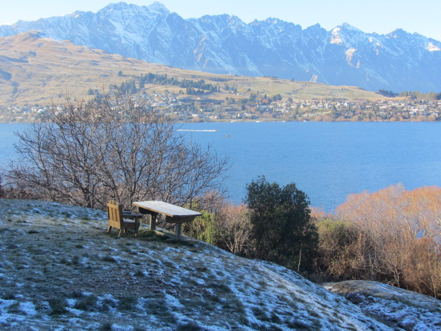 A picture of a table and chair overlooking Lake Wakatipu in Queenstown, New Zealand