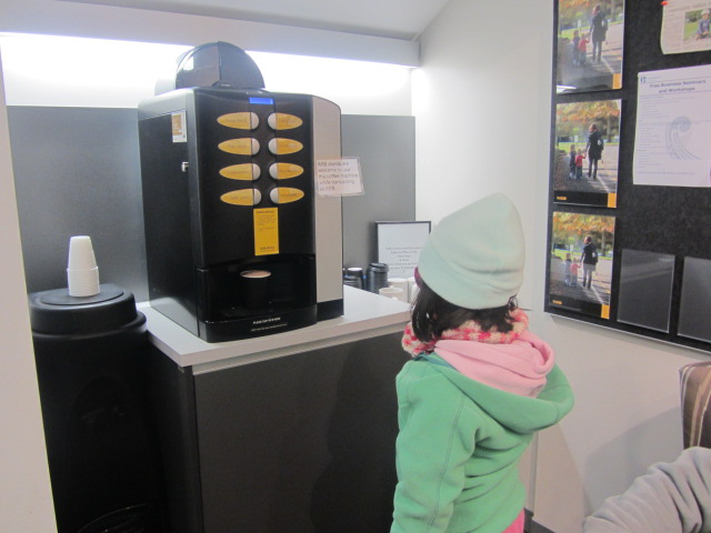 A picture of Amanda waiting for her FREE hot chocolate from a machine in ASB Bank, Queenstown, New Zealand.