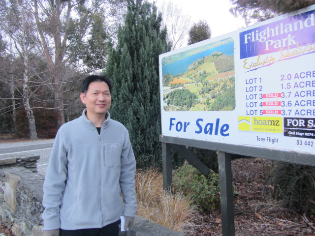 "A picture of HRH with a ""Land For Sale"" sign in Queenstown, New Zealand."