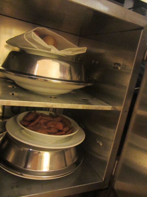 A picture of our hot meals under the room service cart.