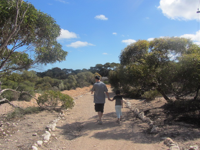 A picture of father and daughter moseying down the rocky path in Eucla, Western Austra