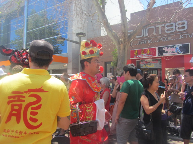 What Chinese New Year is complete without Choy San, God of Prosperity? Here he comes to give out red packets with gold-colored tokens to children.