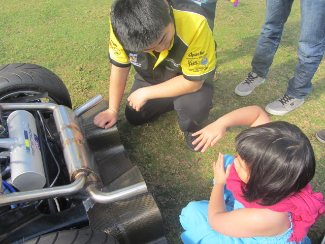 A picture of Amanda checking out a racing car at UWA's open day.