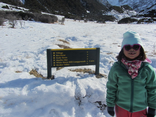 A picture of Amanda with the sign board on the way back to our car at The Hermitage after our trek to Kea Point on Mt Cook in New Zealand.