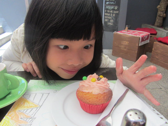 A picture of Amanda marvelling at one of Kit's cupcakes at Not Just Coffee in Sydney